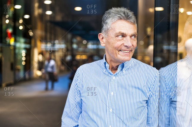Portrait of smiling senior man leaning at glass front in a shopping center