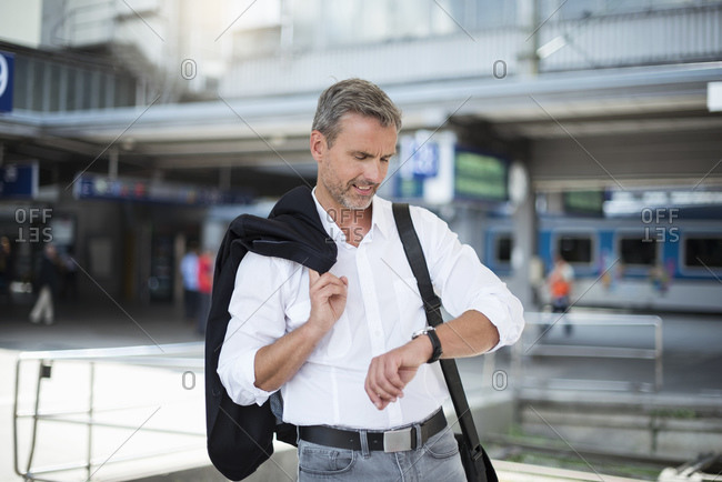 Businessman holding blazer checking time while standing against railroad station
