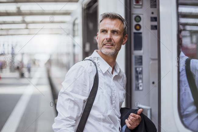 Businessman looking away while entering in train at railroad station platform