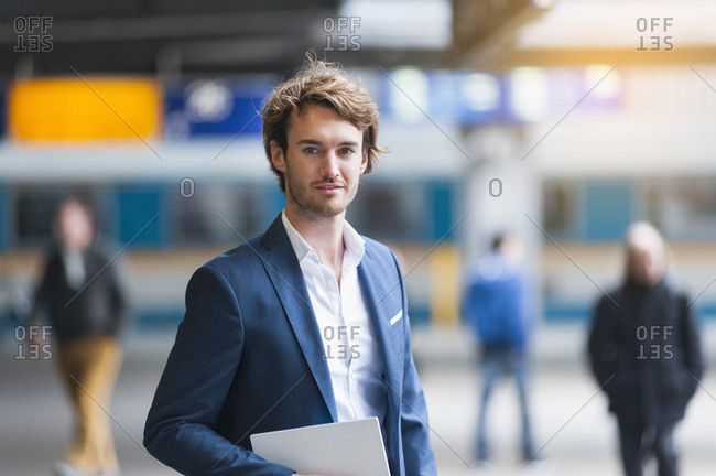 Portrait of young businessman with digital tablet at train station