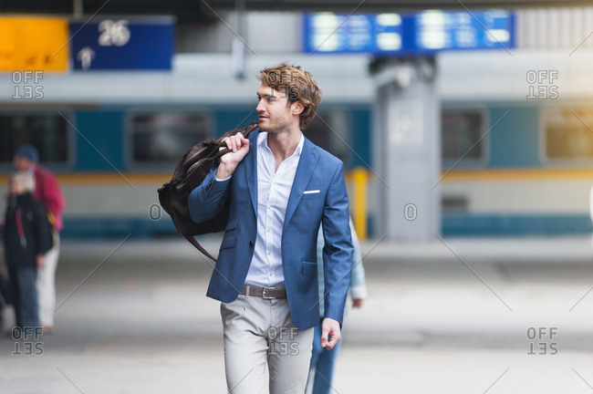 Portrait of young businessman with bag at train station