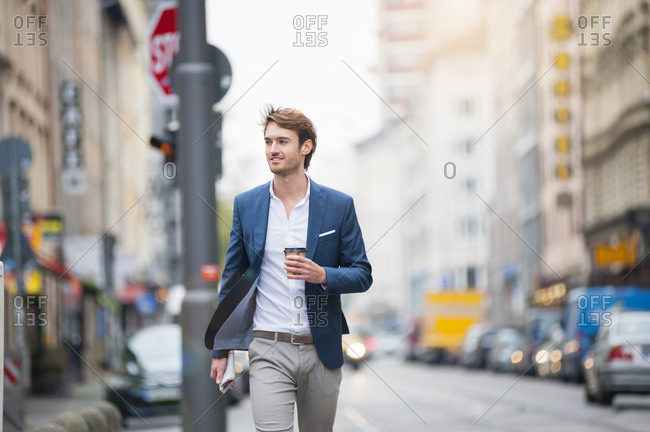 Portrait of young businessman with newspaper and coffee to go walking on the street