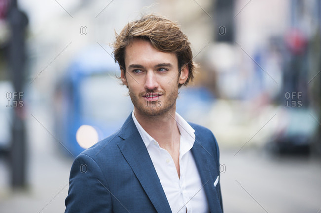 Portrait of young businessman with stubble outdoors