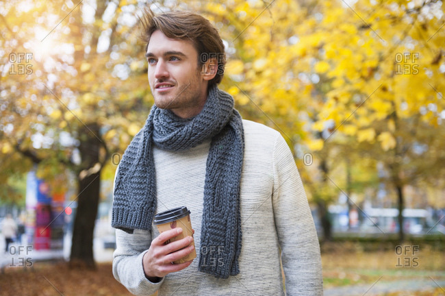 Portrait of young man with coffee to go in autumn