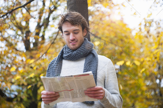 Portrait of young man reading newspaper outdoors