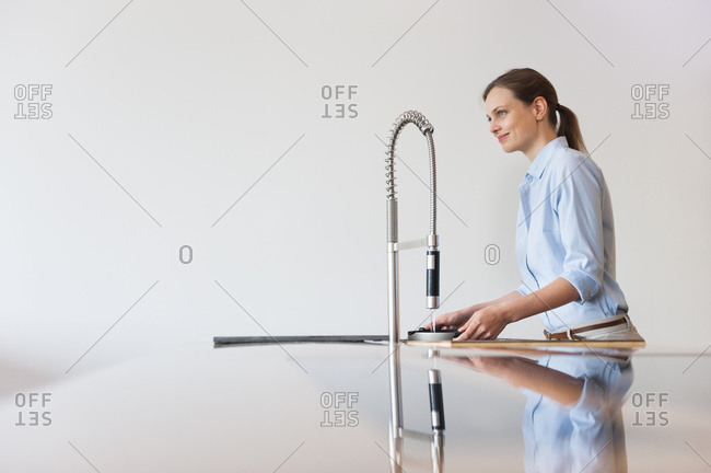 Smiling woman filling water in container through modern kitchen faucet against wall