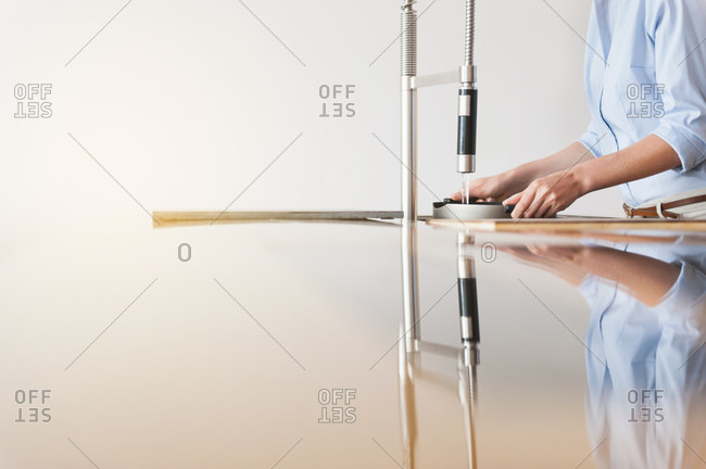 Woman filling water in container through modern kitchen faucet against wall