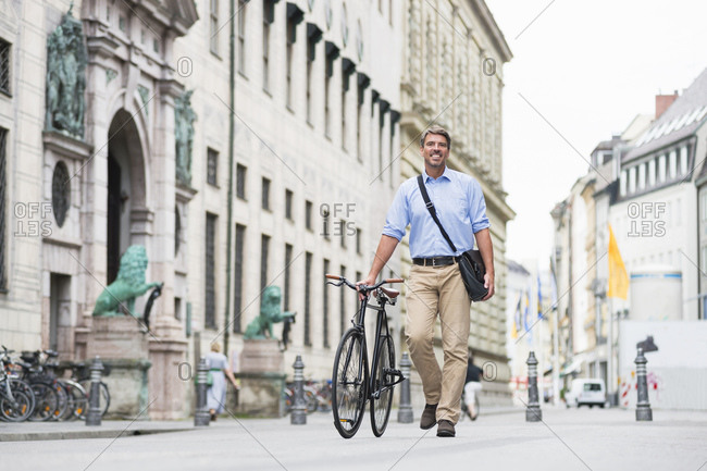 Smiling businessman carrying messenger bag walking with bicycle on street in city