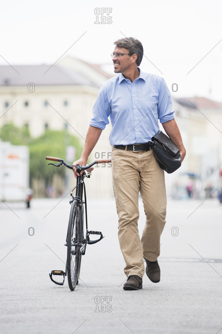 Smiling businessman looking away while walking with bicycle on street in city