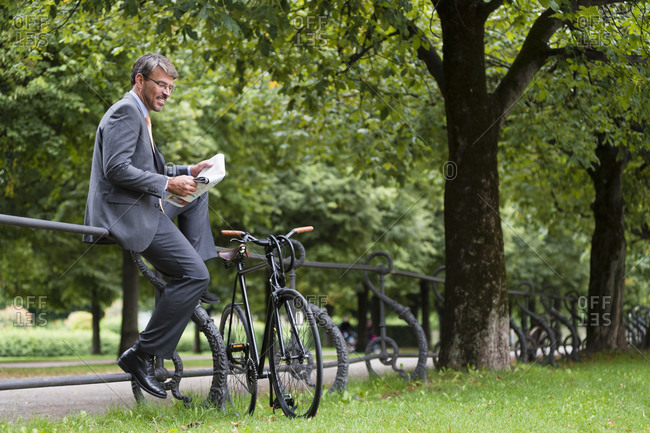 Businessman reading newspaper while sitting on railing in public park