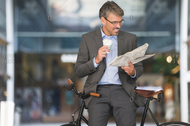 Smiling businessman holding coffee reading newspaper while sitting on bicycle