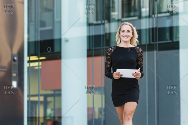 Portrait of happy young businesswoman with digital tablet wearing black mini dress
