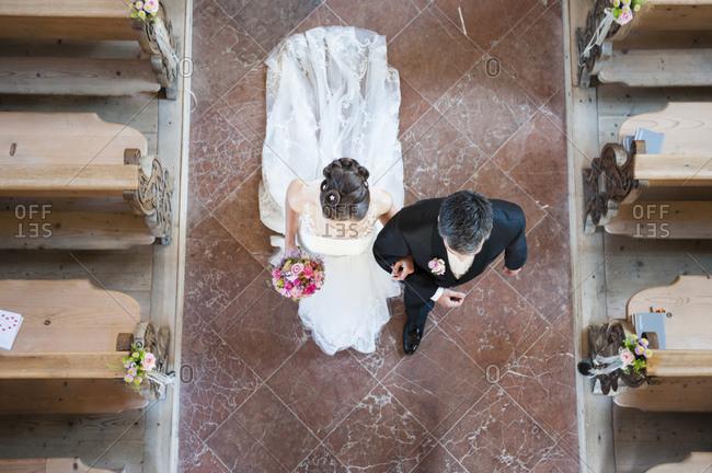 Newlywed couple walking on tiled floor in church