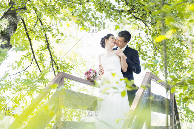 Newlywed couple romancing while standing on footbridge in park