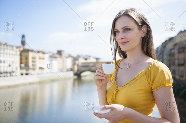 Portrait of smiling woman enjoying espresso near Ponte Vecchio- Florence- Italy