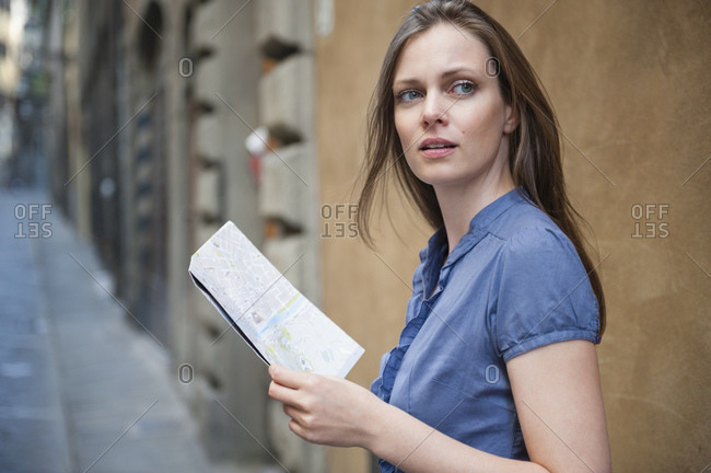 Portrait of woman with city map standing in an alley looking at distance- Florence- Italy