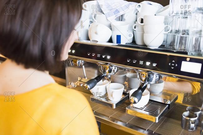 Female barista using espresso maker in coffee shop