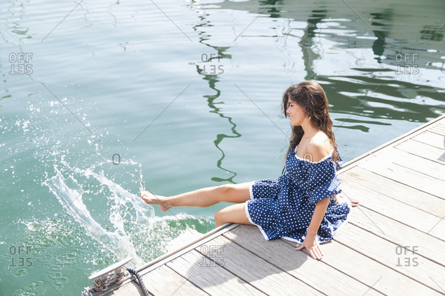 Young woman splashing water in sea with legs while sitting on jetty