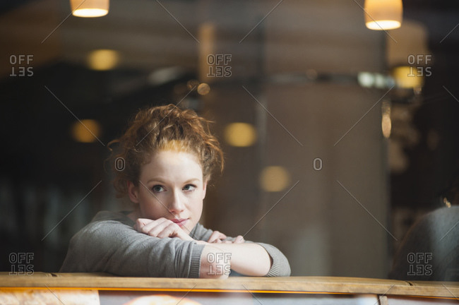 Thoughtful young woman leaning on table seen through glass window in coffee shop