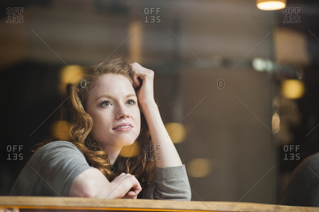 Thoughtful woman leaning on table seen through glass window in coffee shop
