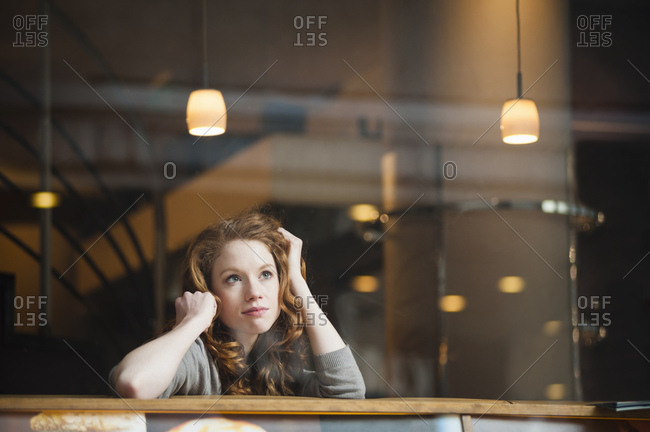 Thoughtful woman leaning on table seen through window in coffee shop