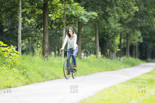Smiling woman riding bicycle on footpath against green trees at park