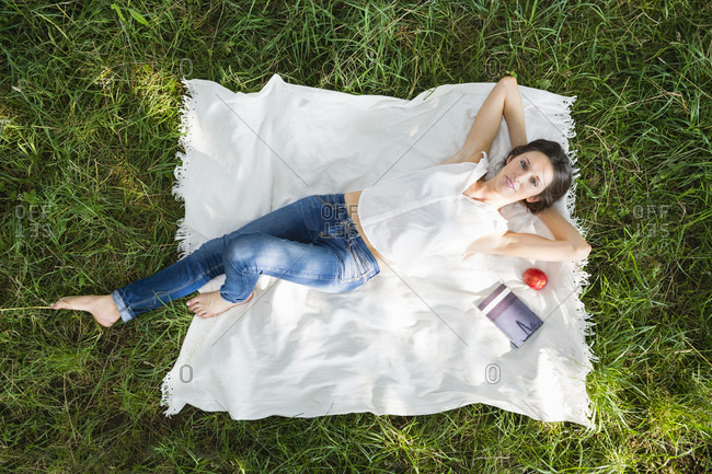Relaxed young woman lying on picnic blanket over grass at park