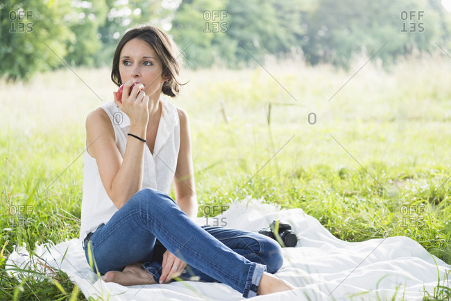 Beautiful young woman eating apple while sitting on picnic blanket at park