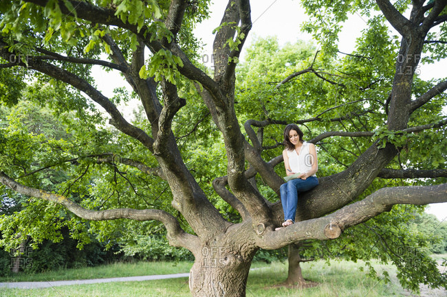 Young woman writing while sitting on tree branch at park