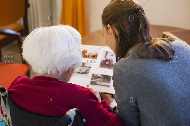 Grandmother with granddaughter looking photo album at home