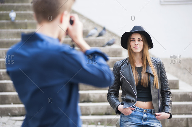 Man photographing fashionable woman through camera on steps in city