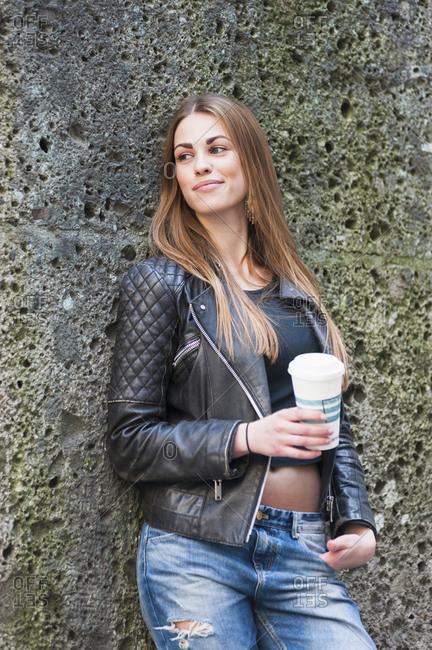 Beautiful young woman holding disposable glass while leaning on weathered wall