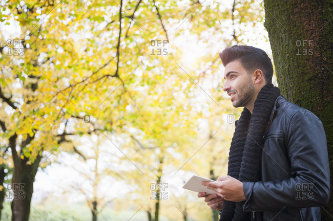 Handsome young man holding digital tablet while looking away and standing tree trunk at park