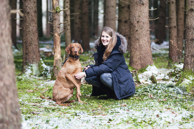 Smiling young beautiful woman crouching by dog against trees in forest