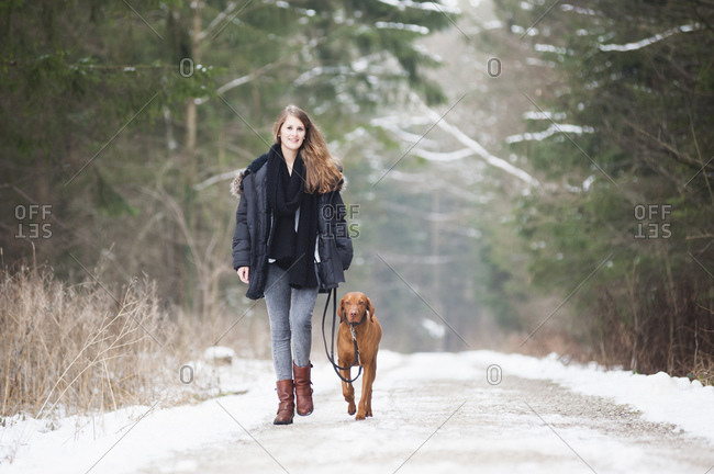 Beautiful young woman walking with dog on road amidst trees in forest during winter