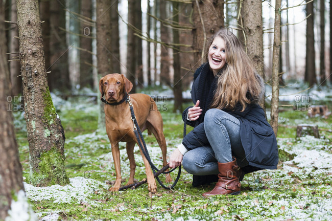 Smiling young beautiful woman with long brown hair crouching by dog against trees in forest