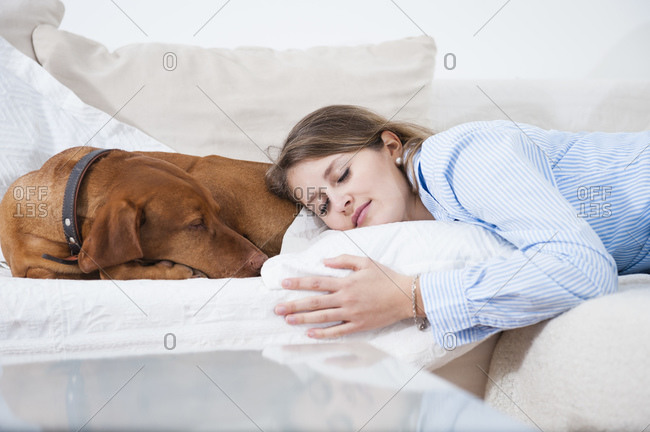 Beautiful young woman sleeping by dog on sofa in living room at home