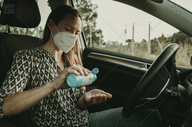 Mid adult woman with protective mask using sanitizer in car