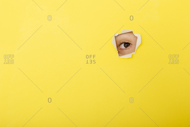 Close-up of boy peeking through torn yellow paper