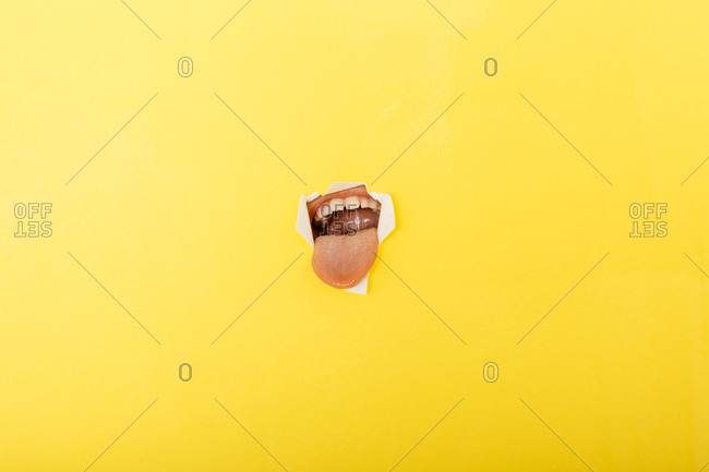Close-up of boy sticking out tongue through torn yellow paper