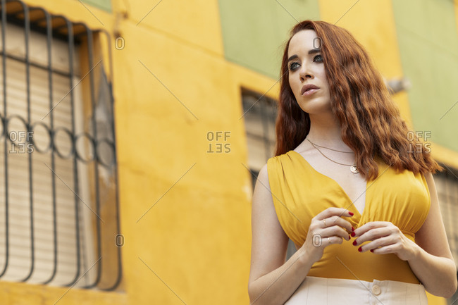 Portrait of redheaded woman wearing yellow top in city