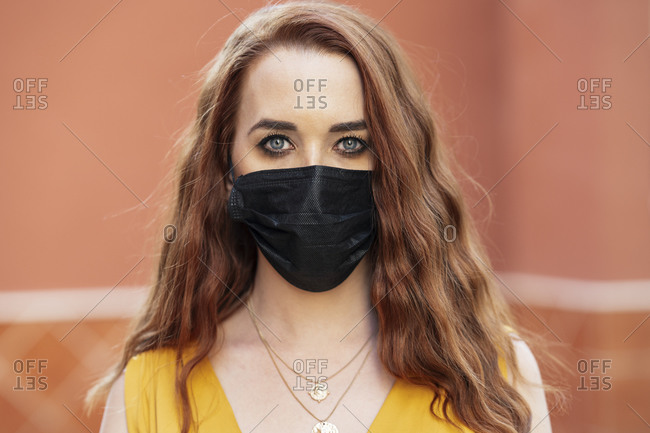 Portrait of redheaded woman with black protective mask outdoors
