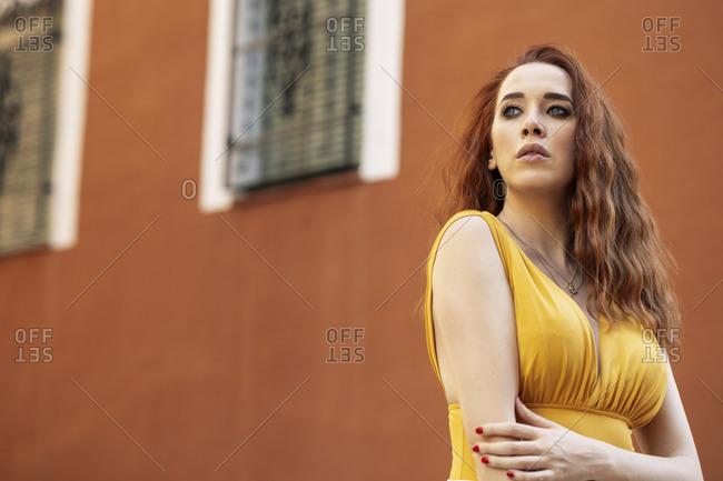 Portrait of serious redheaded woman looking sideways