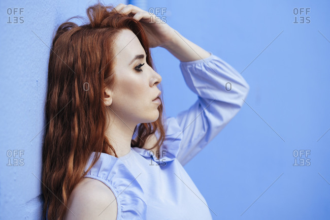 Redheaded woman leaning on blue wall