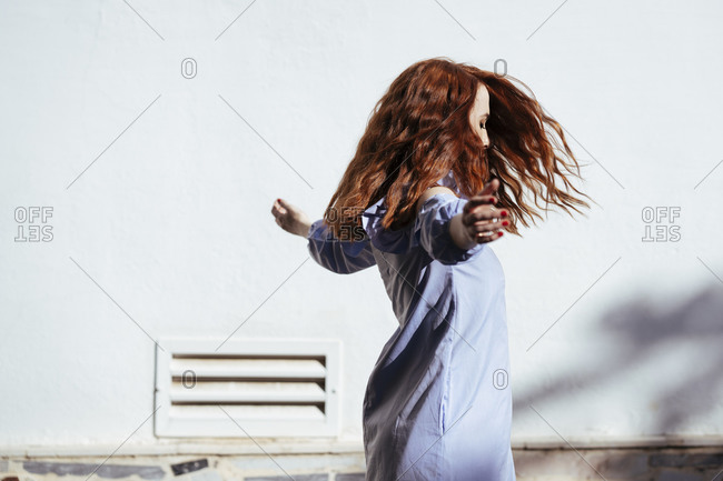 Redheaded woman with raised arms dancing outdoors