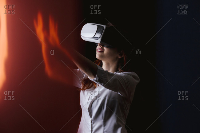 Young woman gesturing while using VR glasses over black background