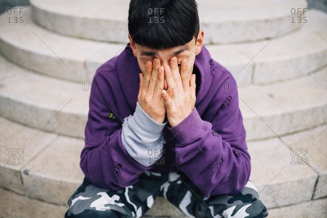 Tired young man rubbing eyes while sitting on steps