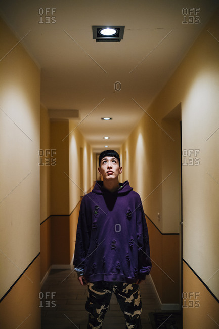 Young man looking at illuminated lighting equipment on ceiling in corridor