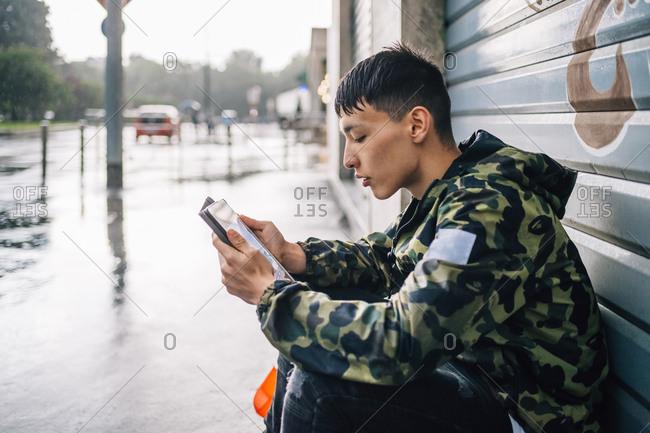 Man using digital tablet against shutter during rainy season
