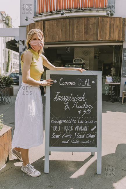 Cafe owner wearing face mask posting a board with Corona special offers